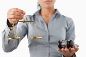 Gavel and scale being held by female lawyer against a white back
